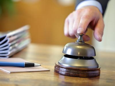 Un barbat apasa pe clopotul din receptia unui hotel